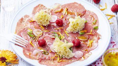 Photo de Carpaccio de bœuf, radis roses et framboises à la Tête de Moine AOP, vinaigrette aux agrumes et tagète mandarine