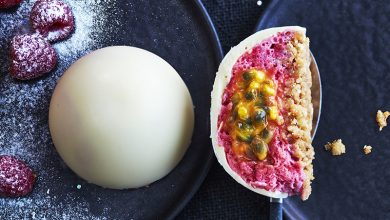 Photo de Dôme de chocolat blanc à la mousse de framboises, cœur au fruit de la passion et croquant de palet breton et pralin